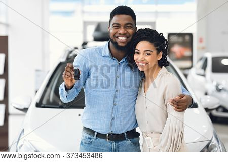 African American Couple Holding New Automobile Key Embracing Standing Near New Family Car In Dealers