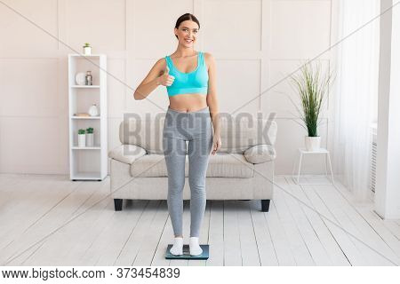 Great Weight Loss. Fit Girl Gesturing Thumbs-up Standing On Weight Scales Weighing Herself At Home.