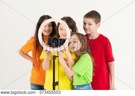 Three Teen Girls And A Boy Smiling And Shoots A Video. Selfies. The Phone Is Mounted On A Tripod And
