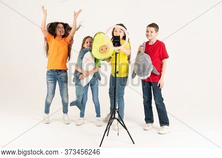 A Group Of Children Bloggers Shoot Video On The Phone. Selfies The Phone Is Mounted On A Modern Roun