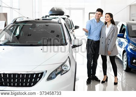 This Is What I Want. Young Family Standing At The Dealership Choosing The Car To Buy, Full Length