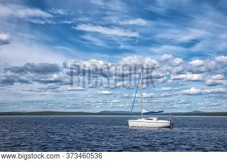 Blue Pacific Lake With Boat With Russian Flag In Boreal Forest In Sunny Day With Many Beautiful Clou