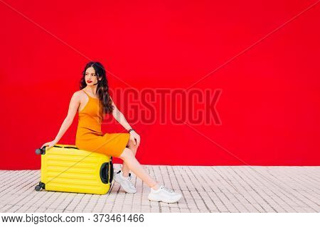 Woman Sitting On Top Of A Yellow Suitcase In Front Of A Red Wall