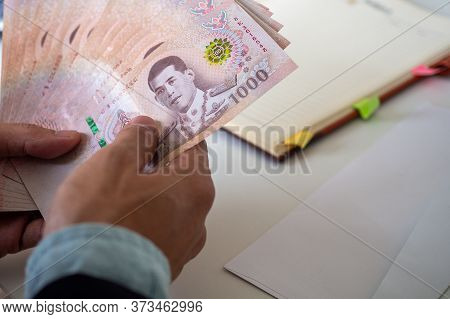 Close Up Of Businessmen Counting Thai Currency. Executive Is Counting Baht, Preparing To Pay Salarie