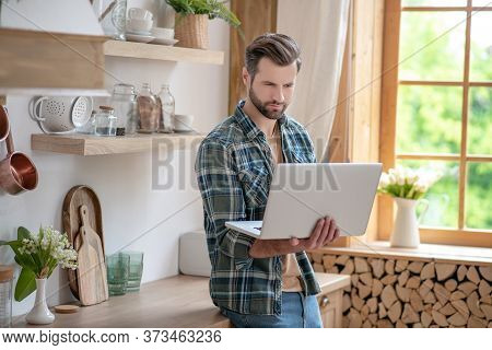 Man In A Checkered Shirt Standing In The Kitchen And Holding A Laptop In His Hands