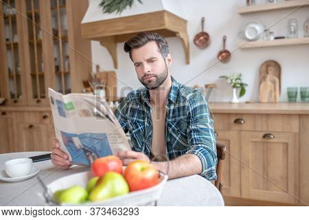 Man In A Checkered Shirt Sitting At The Table, Reading Newspaper And Looking Involved