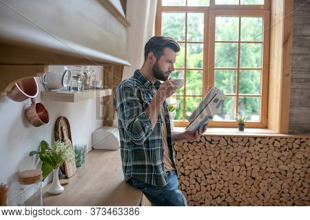 Tall Man In A Checkered Shirt Having Coffee And Reading A Newspaper