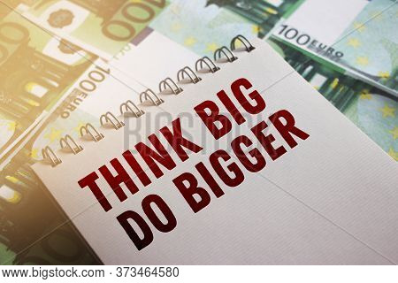 Think Big Do Bigger Printed Words On The Page Of Copybook Put On 100 Euro Banknotes. Selective Focus
