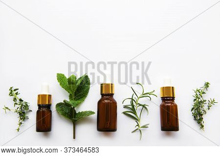 Aromatherapy Concept, Aroma Oil And Herbs - Mint, Rosemary, Thyme On A White Background, Top View