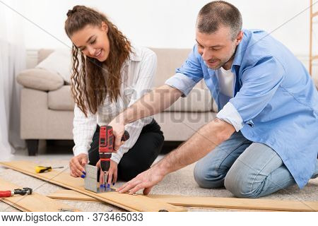 Furniture Assembly. Married Couple Assembling Cabinet Together Sitting On Floor Indoors, Furnishing
