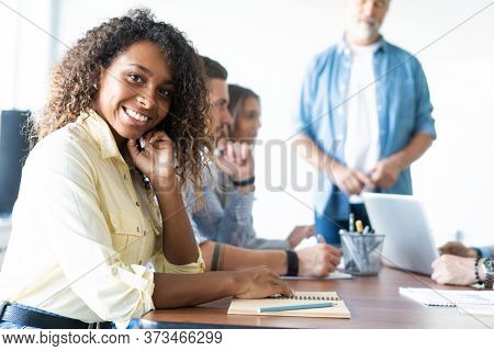 Beautiful Cheerful African Woman Looking At Camera With Smile While Sitting At The Office Table With