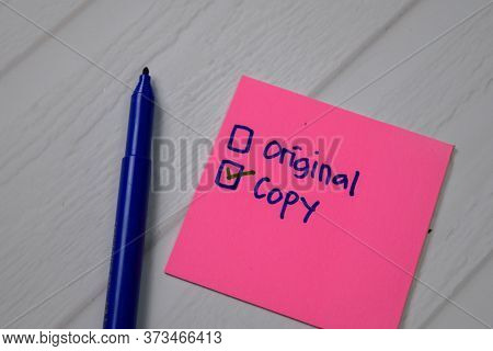 Copy And Original Write On A Sticky Note. Supported By An Additional Services Isolated Wooden Table.