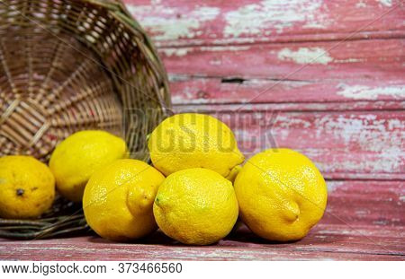 Yellow Sicilian Lemons (citrus X Limon) In Wicker Basket And Wooden Background