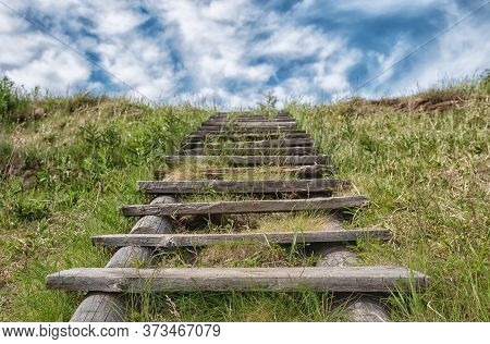 Old Wooden Stairway In Green Grass Stretching Into The Blue Cloudy Sky