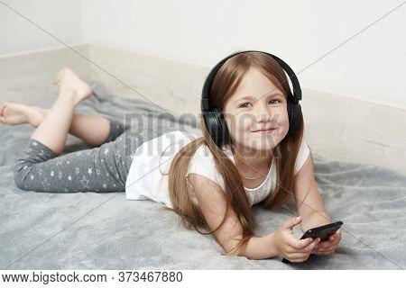 The Little Girl In Headphones. The Girl Is Listening Music. The Little Girl Is Playing Phone.