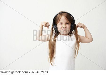 The Little Girl In Headphones. The Little Girl Is Grimacing. The Little Girl With Muscles.