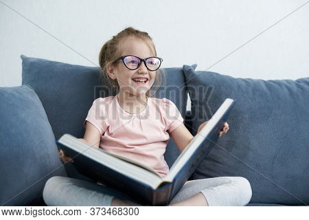 A Little Girl Is Reading Book. A Smiling Little Girl Holds A Book. A Little Girl Is Reading And Smil