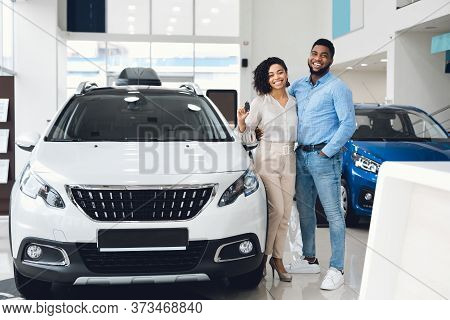 Car Buyers. Joyful Black Couple Hugging Showing Their New Auto Key Standing Near Automobile In Deale
