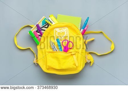 Back To School, Education Concept. Yellow Backpack With School Supplies - Notebook, Pens, Ruler, Cal