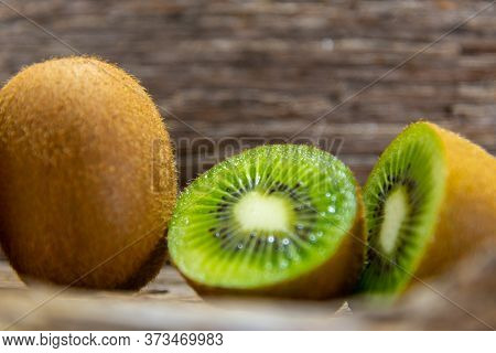 Whole And Halved Kiwi (actinidia Delicious) Fruits On Wooden Background