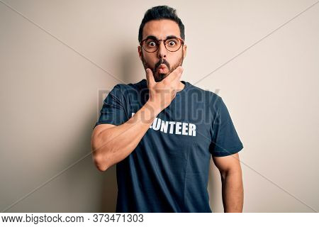 Handsome man with beard wearing t-shirt with volunteer message over white background Looking fascinated with disbelief, surprise and amazed expression with hands on chin