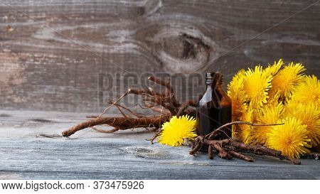 Dandelion Flowers And Roots And Bottle With Extract On  Vintage Wooden Background With Copy Space, M