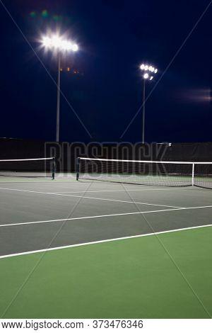 Outdoor tennis court illuminated at night