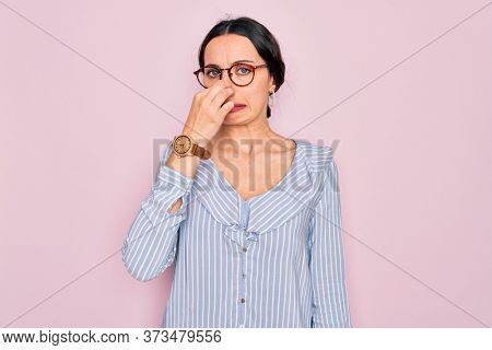 Young beautiful woman wearing casual striped shirt and glasses over pink background smelling something stinky and disgusting, intolerable smell, holding breath with fingers on nose. Bad smell