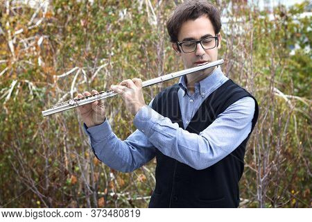 A Male Flutist Playing A Silver Transverse Flute Outdoors, Wearing Eyeglasses.