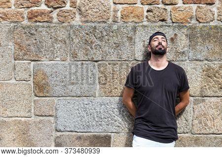 Portrait Of A Man With Beard Leaning On A Stone Wall, Concentrated With His Eyes Closed, Dreaming,