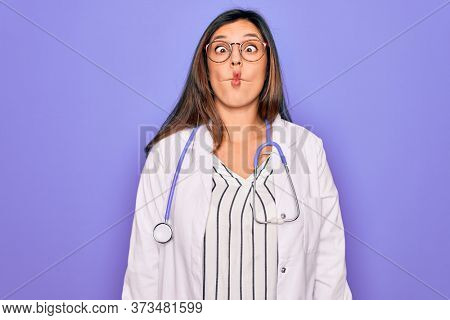 Professional doctor woman wearing stethoscope and medical coat over purple background making fish face with lips, crazy and comical gesture. Funny expression.