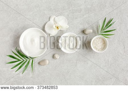 Female Skin And Body Care Cosmetic Products Set: Facial Cream, Cosmetic Clay, Sea Salt On Gray Marbl