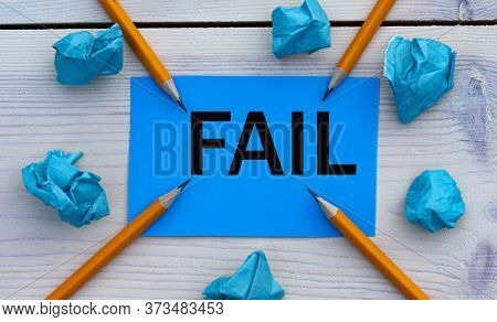 Fail - Word On Blue Paper On A Light Background With Crumpled Pieces Of Paper And Pencils.