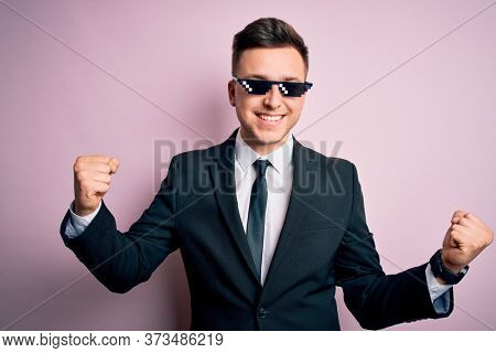 Young handsome caucasian business man wearing funny thug life glasses very happy and excited doing winner gesture with arms raised, smiling and screaming for success. Celebration concept.
