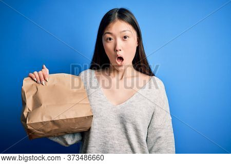 Young asian woman holding delivery paper bag for takeaway food over blue isolated background scared in shock with a surprise face, afraid and excited with fear expression