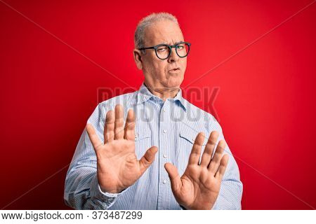 Middle age handsome hoary man wearing casual striped shirt and glasses over red background Moving away hands palms showing refusal and denial with afraid and disgusting expression. Stop and forbidden.