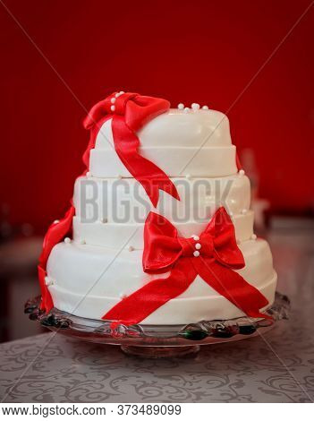 Tall Three-tier Cake, White With Red Bows On A Glass Plate On Red Background. Celebration, Wedding,