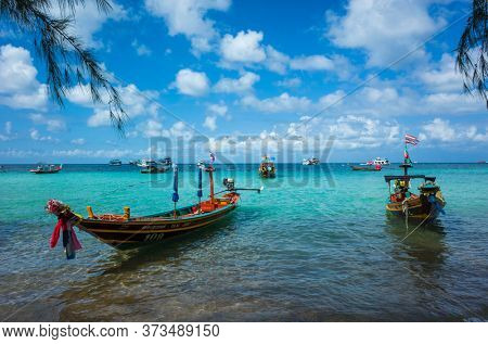Koh Tao, Thailand - January 27, 2020: Long tail boats water taxi in turquoise clear water at Sairee beach. Tropical island paradise