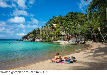 Koh Tao, Thailand - January 27, 2020: Tropical island paradise, Tourist couple enjoying sun and turquoise clear water at Sairee beach