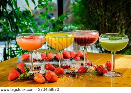 Variety of refreshing summer cocktails in glasses covered with fresh strawberries on a table. Concept for traditional italian cocktails - fragolino, sgroppino, rossini