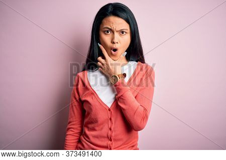 Young beautiful chinese woman wearing casual sweater over isolated pink background Looking fascinated with disbelief, surprise and amazed expression with hands on chin