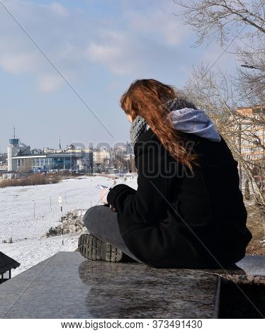 Omsk, Russia -march 2016: A Girl With A Smartphone On The Background Of The Winter Embankment Of Irt