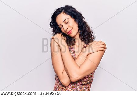 Young beautiful hispanic woman wearing casual clothes hugging oneself happy and positive, smiling confident. self love and self care