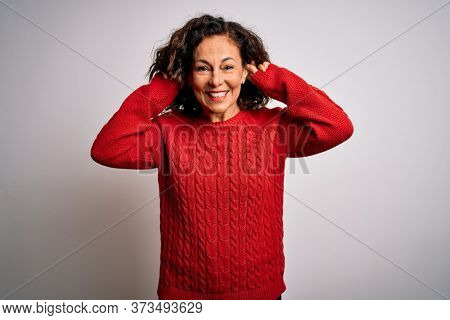 Middle age brunette woman wearing casual sweater standing over isolated white background Smiling pulling ears with fingers, funny gesture. Audition problem