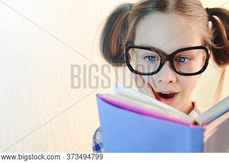 Girl Schoolgirl With Glasses On Her Face With Delight Reads A Book.