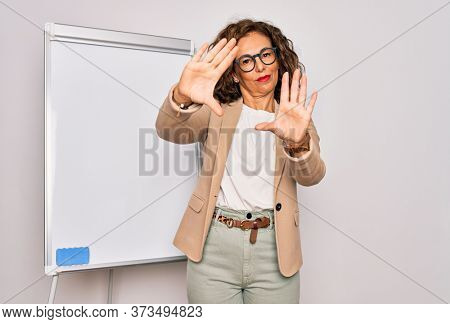 Middle age senior business woman standing on seminar presentation by magnectic blackboard doing frame using hands palms and fingers, camera perspective