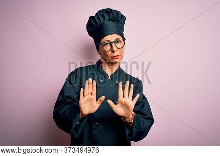 Middle age brunette chef woman wearing cooker uniform and hat over isolated pink background Moving away hands palms showing refusal and denial with afraid and disgusting expression. Stop and forbidden