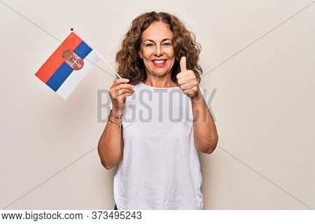 Middle age beautiful patriotic woman holding serbian flag over isolated white background smiling happy and positive, thumb up doing excellent and approval sign