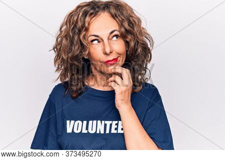 Middle age woman asking for social care wearing volunteer t-shirt over white background thinking concentrated about doubt with finger on chin and looking up wondering