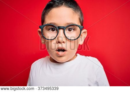 Young little smart boy kid wearing nerd glasses over red isolated background scared in shock with a surprise face, afraid and excited with fear expression